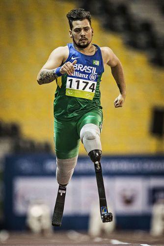 Descrição: Foto na vertical. O atleta Alan Fonteles corre na pista de atletismo com duas próteses para as pernas. Utiliza um short verde e uma camiseta regata do Brasil. Sua pele é claro e seus cabelos escuros e curtos. Fim da descrição