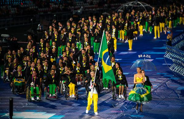 Imagem na horizontal. Entrada da delegação brasileira nos Jogos Paralímpicos Londres 2012. O porta-bandeiras é Daniel Dias, atrás dele vem os demais atletas em multidão. Fim da descrição