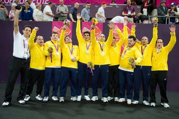 Foto na horizontal. Time de Goalball nas Paralimpíadas Londres, 2012. Na foto há dez homens. O primeiro da esquerda é o treinador, que veste calça preta e camiseta branca. Os nove seguintes, os jogadores, estão com calças azuis marinho, blusas de manga comprida amarelas do Brasil e com suas medalhas de prata no pescoço.Fim da descrição