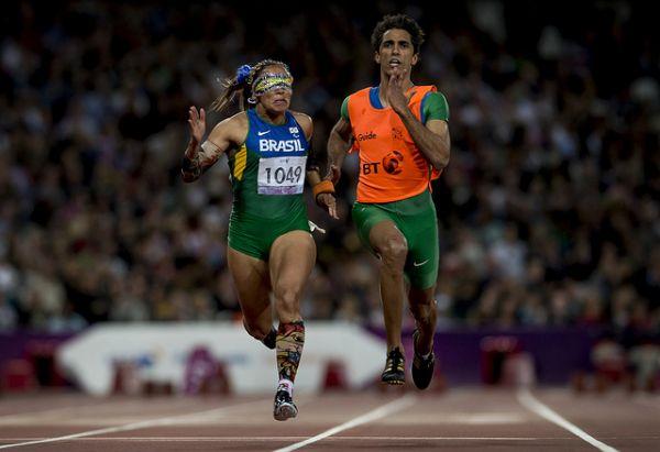 Correndo na pista de atletismo, na final dos 100m, categoria T11, nos Jogos Paralímpicos Londres 2012, estão Terezinha Guilhermina à esquerda, utilizando um macacão da seleção brasileira e seus adereços tradicionais, como meias coloridas e tapa olho enfeitado, e à direita seu guia Guilherme Soares, utilizando o mesmo macacão com um colete laranja sobreposto. Fim da descrição