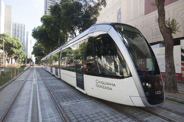 Imagem do trem VLT (Veículo Leve sobre Trilhos), novo meio de transporte do Rio de Janeiro, nos trilhos em meio à cidade. Fim da descrição.
