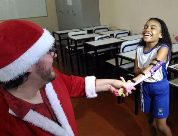 A imagem está no formato retangular na horizontal. Nela contém o jovem Thiago Jucá, vestido da Papai Noel, ajoelhado em uma sala de aula, na frente de uma garota que está feliz por receber uma prótese personalizada. Fim da descrição.