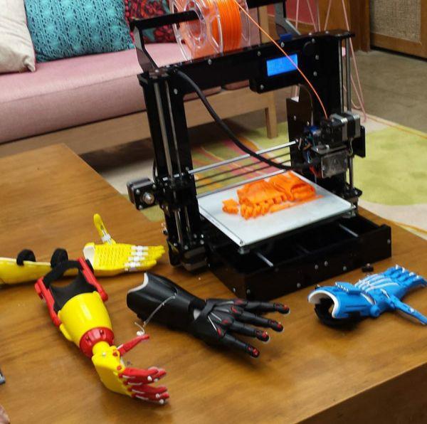 A imagem está no formato retangular na horizontal. Nela contém um uma mesa de madeira do cenário do programa É de casa e sobre ela, tem uma impressora 3D e três próteses espalhadas. Fim da descrição.