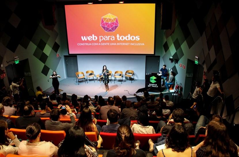 Foto de um auditório lotado, visto de cima. No palco, há uma mulher morena que fala ao público, com uma tela ao fundo que projeta o logo do Movimento Web para Todos