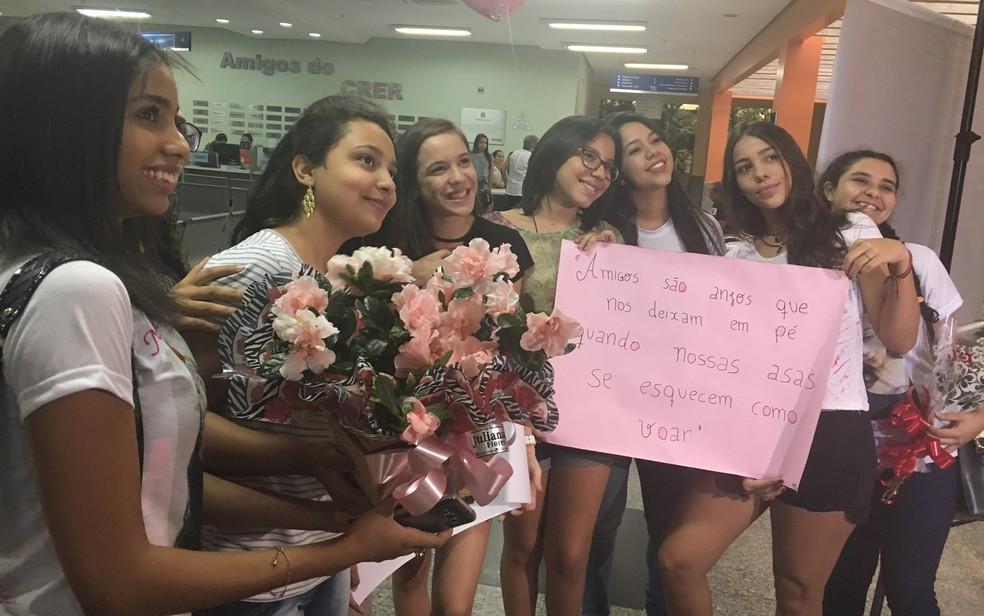 Amigas de Isadora de Morais levaram flores e cartazes para homenagear estudante, no Crer (Foto: Vanessa Martins/G1)