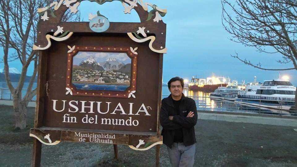 Luiz em frente à placa que indica Ushuaia
