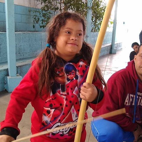 garota tocando berimbau na capoeira adaptada